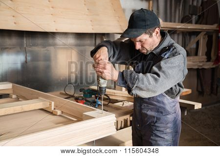 Carpenter assembles wooden furniture in the carpentry shop. Focus on the hand drill.