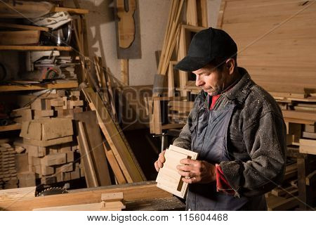 Carpenter works with wood in the carpentry workshop. Focus on wooden part.