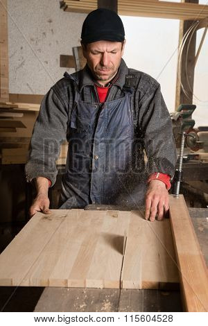 Carpenter sawing a board in the circulation saw in a carpenter's workshop.