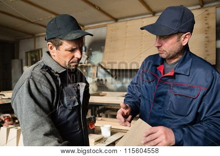 Supervisor and worker to discuss the process of making wood products for furniture.