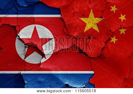 Flags Of North Korea And China Painted On Cracked Wall