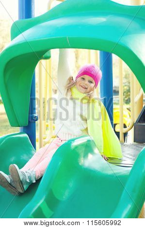 Happy girl play on slide playground in the autumn park.