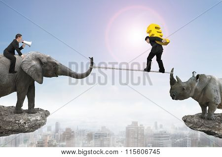 Man Riding Elephant Against Rhinoceros Another Man Carrying Euro Sign