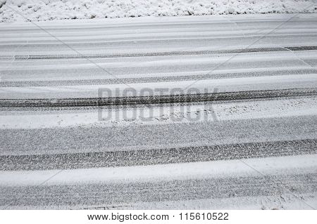 tire tracks on street after snow