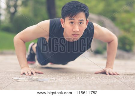 Young Asian Man doing push ups outdoor