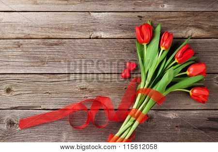 Red tulips and candy hearts over wooden table. Valentines day background. Top view with copy space