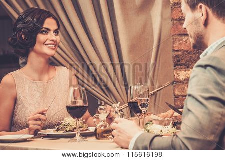 Stylish wealthy couple enjoying meal at restaurant.