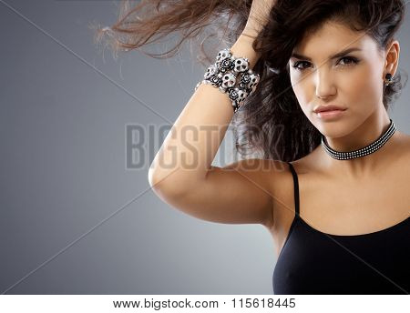 Portrait of beautiful, sexy looking wild woman, looking at camera hand in hair.