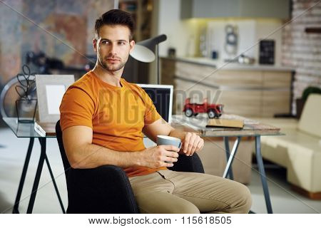 Handsome young man holding tea mug, daydreaming at home.