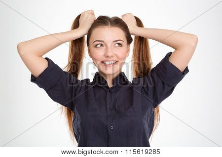 Happy amusing young woman with two tails having fun over white background