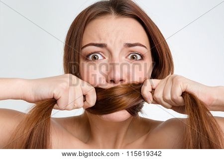Closeup portrait of scared frightened young woman covered her mouth with her long hair over white background