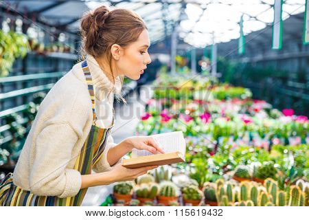 Profile of serious pretty young woman with book working in garden center