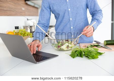 Closeup of man in blue shirt using laptop and making salad in glass bowl on the kitchen