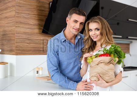 Beautiful couple holding paper packet of food standing on the kitchen