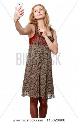 Satisfied Blonde Girl In A Beautiful Dress Smiles And Makes Selfie On The Smartphone