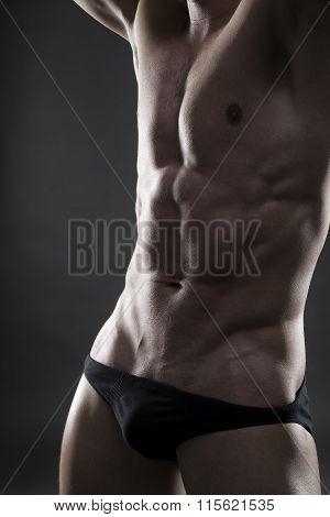 Handsome Muscular Bodybuilder Posing On Gray Background. Low Key Close Up Studio Shot