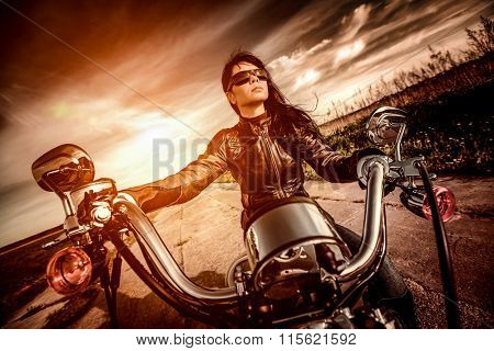 Biker girl in a leather jacket on a motorcycle looking at the sunset. Filter applied in post-production.