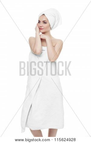 Gorgeous girl with dark hair and eyebrows, wearing white towel on head, holding hands near face. lig