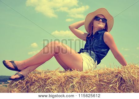 Woman with hat  on a bale of straw
