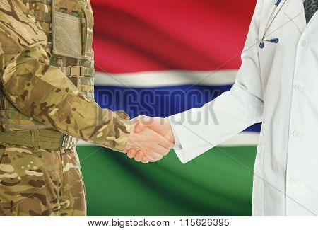 Military Man In Uniform And Doctor Shaking Hands With National Flag On Background - Gambia