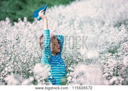Happy Boy Holds In Hand Blue Paper Airplane On Bright Sunny Day