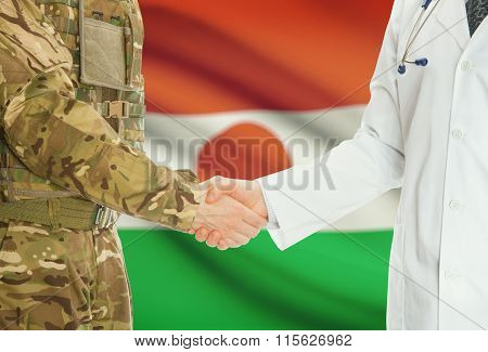 Military Man In Uniform And Doctor Shaking Hands With National Flag On Background - Niger