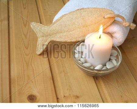 Towel,luffa Wisp And Burning Candle On The Wooden Background
