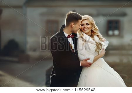 Happy Newlywed Groom Hugging Blonde Beautiful Bride From Behind At Sunset In The City