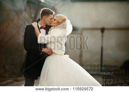 Happy Newlywed Groom Hugging And Kissing Blonde Beautiful Bride At Sunset In The City