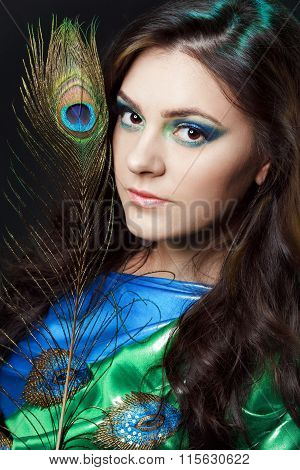Close Up Beauty Portrait Of Beautiful Girl With Peacock Feather. Creative Makeup Peafowl Feathers