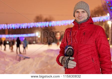 Mature man with skates against a skating rink