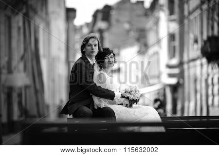 Romantic Couple Of Bride And Groom Sitting And Posing In Old Town Street B&w