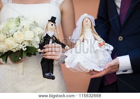 Happy Bride And Groom Holding Cute Handmade Dolls Of Husband And Wife Closeup