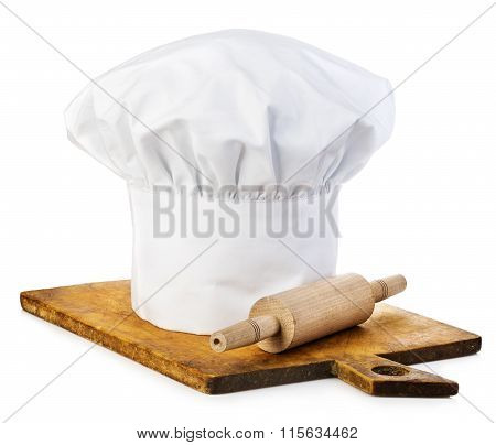 Original Cooks Cap With Wooden Rolling-pin On A Wooden Cutting Board.