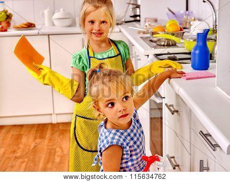 Children wash dishes and furniture in kitchen.