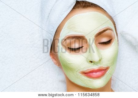 Spa Woman applying Facial clay Mask. Beauty Treatments. Close-up portrait of beautiful girl with a towel on her head applying facial mask