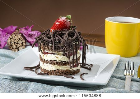 Strawberry and chocolate cake with coffee mug at the background, on table.