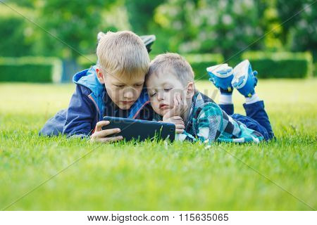 Siblings Using A Tablet, Yingon Grass In The Park In Suny Day