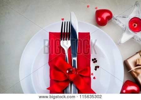 Valentine's Day Romantic Dinner table setting. Date. St. Valentine table served, decorated with bright red hearts, satin ribbon and candles