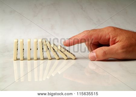 Row Of Dominoes Pushed By Hand