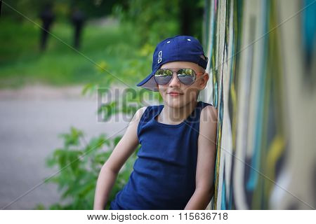 Fashionable Little Boy In Sunglasses And Cap.graffiti Background