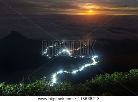 Illuminated walkway to the top of the mountain of Adam's peak with clouds over the lower areas of Sri Lanka. View from Adam's Peak at night