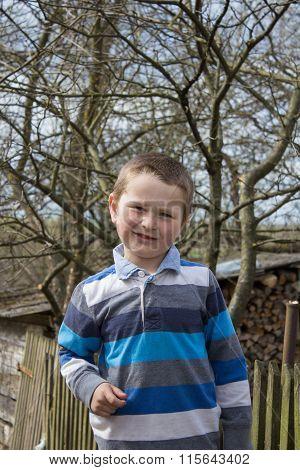 Little Boy Near The Fence In The Village