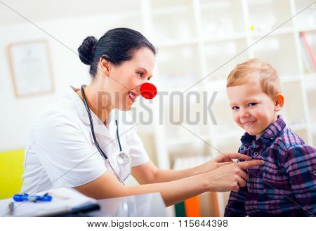 Doctor pediatrician with clown nose and  happy child patient