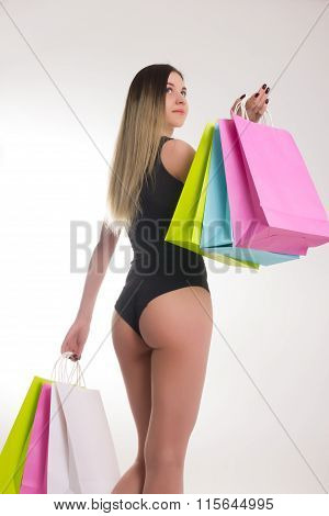 Shopping woman holding shopping bags. Closeup of beautiful woman legs in a bathing suit