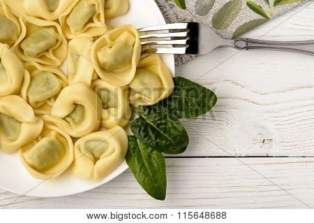 Tortellini with spinach and ricotta on wooden table.
