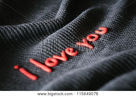 Confession of Love. Phrase of red letters on black fabric