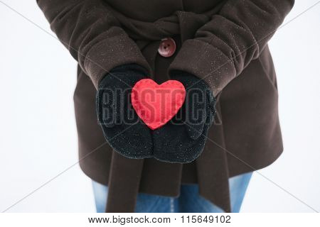 Girl holding a red decorative heart in his hands