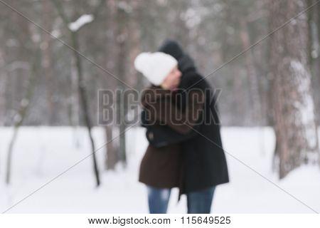 Love story. Happy couple in an embrace. Walk in park. Photo in defocusing