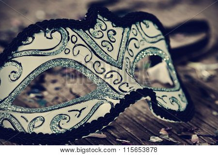 an elegant blue and black carnival mask on a rustic wooden surface, with a filter effect